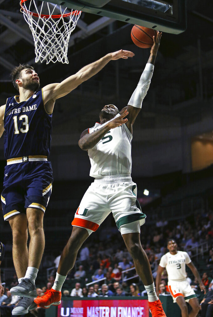 Miami guard Zach Johnson (5) goes to the basket against Notre Dame guard Nikola Djogo (13) during the second half of an NCAA college basketball game, Wednesday, Feb. 6, 2019 in Coral Gables, Fla. (David Santiago/Miami Herald via AP)