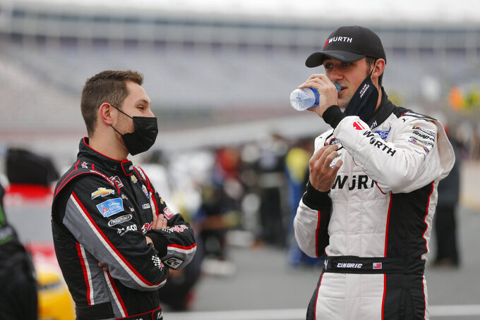 Kaz Grala, left, talks with Austin Cindric before a NASCAR Xfinity Series auto race at Charlotte Motor Speedway in Concord, N.C., Saturday, Oct. 10, 2020. (AP Photo/Nell Redmond)