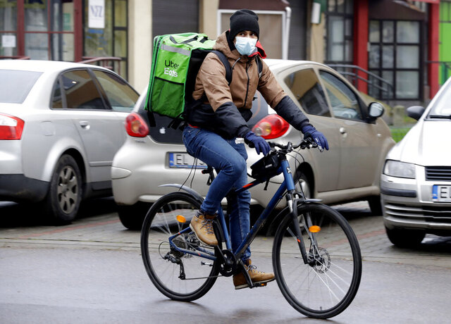 Venezuela's 2012 Olympic champion in fencing, Ruben Limardo Gascon, cycles with a food delivery to clients in Lodz, Poland, Saturday, Nov. 14, 2020. Limardo Gascon needs the delivery job to support his family as he lives and trains in Poland and plans to win a medal at upcoming Tokyo Olympics. (AP Photo/Czarek Sokolowski)