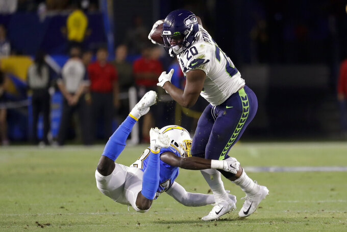Seattle Seahawks running back Rashaad Penny, breaks away from Los Angeles Chargers defensive back Brandon Facyson during the first half of an NFL preseason football game Saturday, Aug. 24, 2019, in Carson, Calif. (AP Photo/Alex Gallardo)