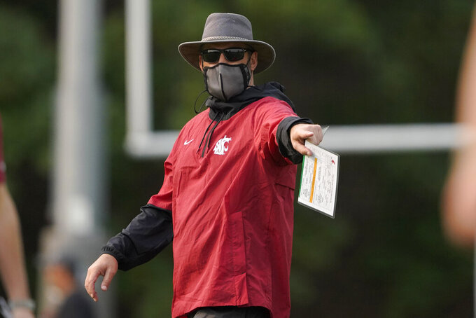 Washington State head coach Nick Rolovich wears a mask as he gives directions during the first day of NCAA college football practice, Friday, Aug. 6, 2021, in Pullman, Wash. (AP Photo/Ted S. Warren)