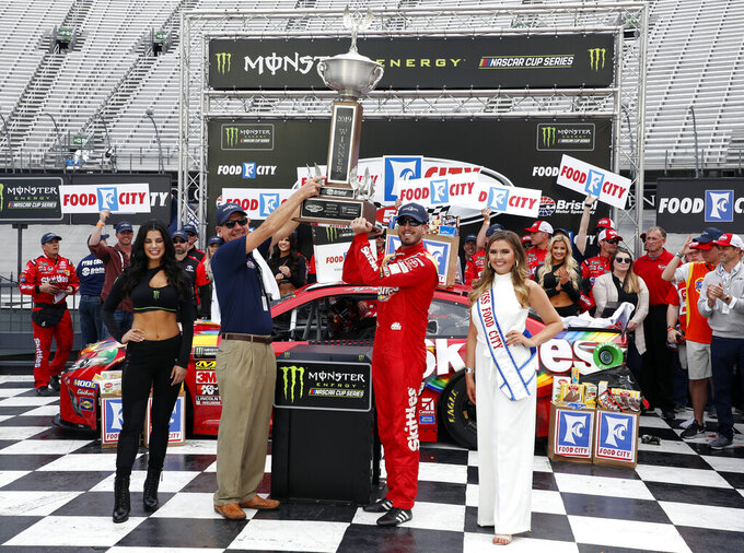 Driver Kyle Busch (18) hoists the trophy with Steve Smith, president and CEO of Food City after winning a NASCAR Cup Series auto race, Sunday, April 7, 2019, in Bristol, Tenn. (AP Photo/Wade Payne)