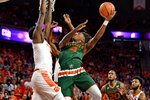 Miami's Lonnie Walker IV drives to the basket while defended by Clemson's Elijah Thomas during the first half of an NCAA college basketball game Saturday, Jan. 13, 2018, in Clemson, S.C. (AP Photo/Richard Shiro)