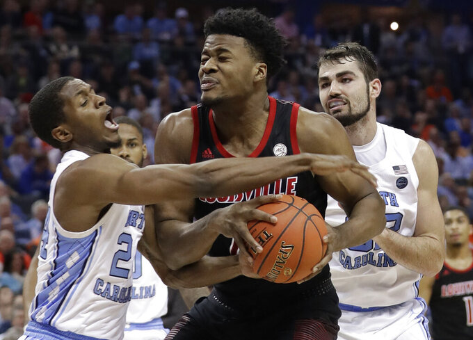 Louisville's Steven Enoch, center, is trapped by North Carolina's Kenny Williams, left, and Luke Maye, right, during the second half of an NCAA college basketball game in the Atlantic Coast Conference tournament in Charlotte, N.C., Thursday, March 14, 2019. (AP Photo/Chuck Burton)