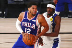 Philadelphia 76ers forward Tobias Harris (12) drives to the basket against against Indiana Pacers forward Justin Holiday (8) during the fourth quarter of an NBA basketball game Saturday, Aug. 1, 2020, in Lake Buena Vista, Fla. (Kim Klement/Pool Photo via AP)