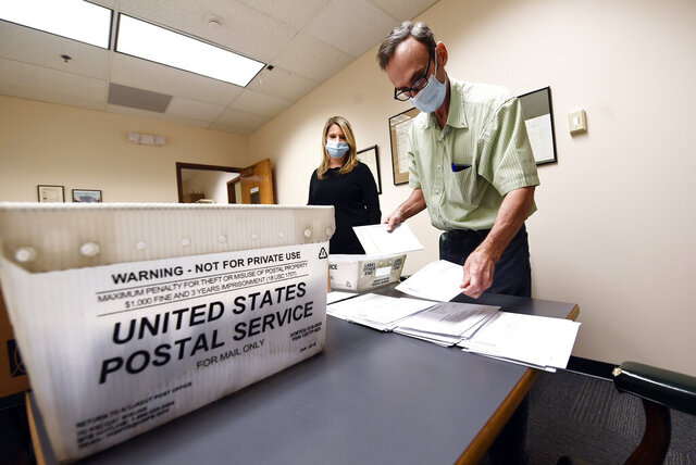 Republican commissioner Rachel Bledi ,left, and Frank Bongiorno sort Absentee Ballots at the Albany County Board of Elections building Wednesday, Oct. 14, 2020, in Albany, N.Y. (AP Photo/Hans Pennink)