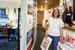 In this June 22, 2020, photo, Kate Bolz, Democratic candidate for Nebraska's 1st Congressional District, poses for a photo among election placards and the photos of President John F. Kennedy, left, and Sen. Jim Exon, a Democrat who never lost an election, at the Lancaster County Democratic Party offices in Lincoln, Neb. State Democrats have taken a lot of proactive steps in recent years to try to expand the party and win elections, but with Democrats now accounting for 29% of the state's registered voters, running as a Democrat in Nebraska is tough. (AP Photo/Nati Harnik)
