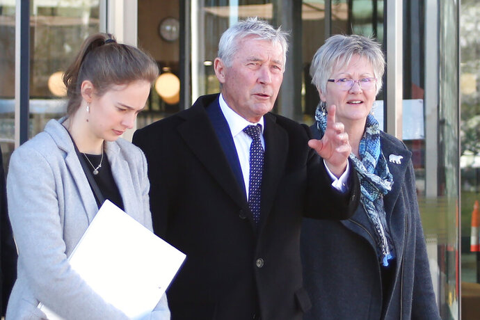 Lawyer Bernard Collaery, center, leaves the Australian Capital Territory Supreme Court in Canberra, Australia, on Thursday, Aug. 22, 2019. Collaery  is one of two whistleblowers who appeared in the court charged separately with leaking classified government information that alleges Australia bugged of East Timor's Cabinet and potential war crimes committed by Australian troops in Afghanistan. (AP Photo/Rod McGuirk)