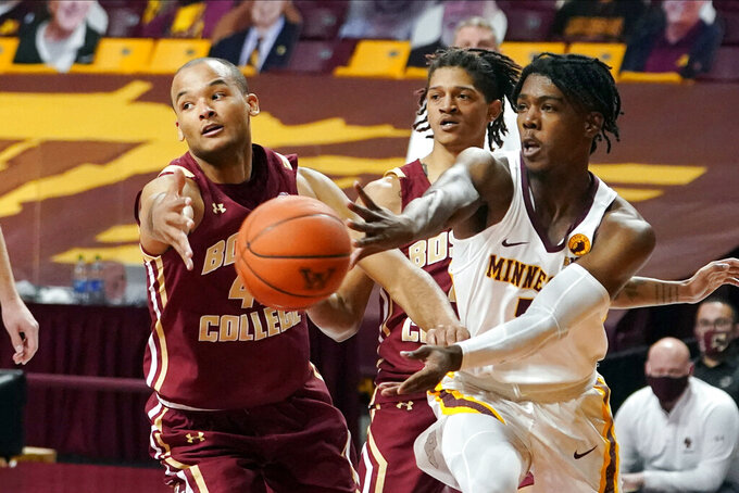 Minnesota's Marcus Carr, right, gets off a pass as Boston College's Steffon Mitchell defends during the first half of an NCAA college basketball game Tuesday, Dec. 8, 2020, in Minneapolis. (AP Photo/Jim Mone)