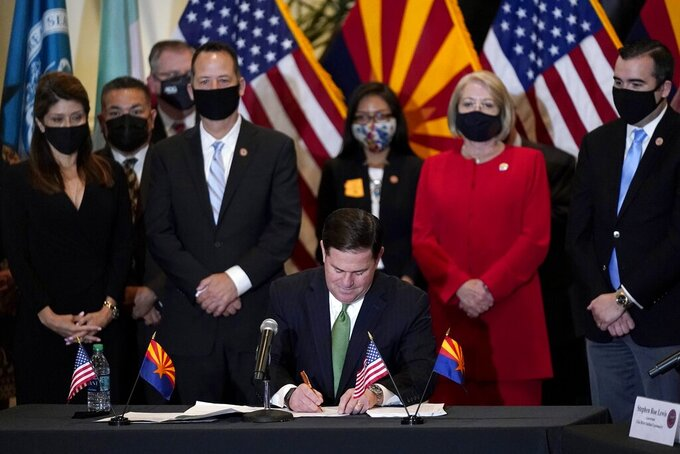 With Arizona legislators looking on, Republican Arizona Gov. Doug Ducey puts his signature on a bill at a bill signing allowing a major expansion of sports betting in Arizona at an event at the Heard Museum Thursday, April 15, 2021, in Phoenix. The measure approved by the Legislature adds additional types of table games at tribal casinos and for the first time allows sports betting under licenses issued to tribes and pro sports teams. (AP Photo/Ross D. Franklin)