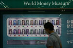 A visitor wearing a face mask walks in front of a bank's currency advertisement board in Seoul, South Korea, Thursday, Aug. 12, 2021. Asian shares were mixed Thursday as caution set in among investors following another wobbly day of trading on Wall Street.  (AP Photo/Lee Jin-man)