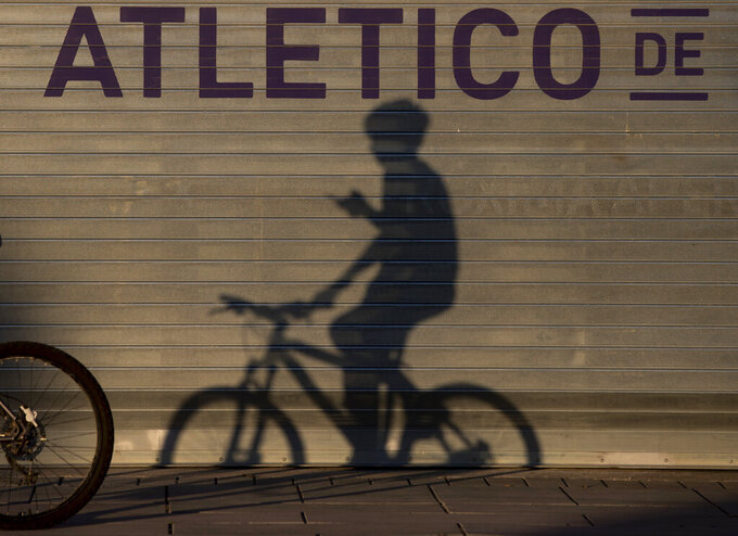 A boy casts a shadow as he cycles past Atletico Madrid's Wanda Metropolitano stadium in Madrid, Spain, Tuesday, May 5, 2020. The Spanish soccer league aims to restart in June without spectators. It's new compulsory protocols say all players, coaches and club employees must be tested for COVID-19 coronavirus before training resumes, then regularly after that. All clubs' training facilities must be properly prepared and disinfected before players can start practicing individually. (AP Photo/Paul White)