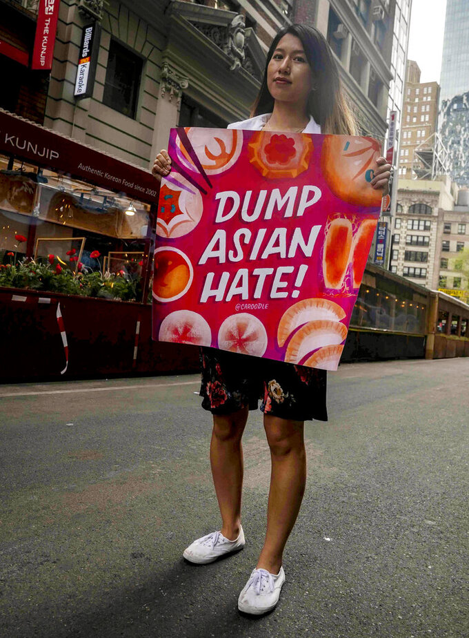 Ida Chen, a physician assistant student, unfold a banner she carry at rallies protesting anti-Asian hate, Saturday April 24, 2021, in New York's Chinatown. Chen, who is American-born Chinese, join medical professionals of Asian and Pacific Island descent who feel the anguish of being racially targeted because of the virus while toiling to keep people from dying of it. (AP Photo/Bebeto Matthews)