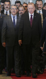 Turkish President Recep Tayyip Erdogan, center right, and Algerian Prime Minister Abdelaziz Djerad arrive for a meeting Sunday, Jan.26, 2020 in Algiers. Turkish President Recep Tayyip Erdogan visited Algeria for talks on the conflict in neighbouring Libya. (AP Photo/Fateh Guidoum)