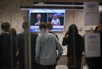 """Staff in the green room watch a television screen showing presenters Andrew Neil and Michelle Dewberry broadcast from a studio, during the launch event for new TV channel GB News in London, Sunday June 13, 2021. A new news channel launched on British television on Sunday evening with the aim of giving a voice """"to those who feel sidelined or silenced."""" GB News, which is positioning itself as a rival to the news and current affairs offerings of the likes of BBC and Sky News, denies it will be the British equivalent of Fox News. However, it clearly wants to do things differently. (Yui Mok/PA via AP)"""