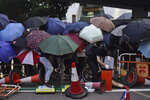 Protesters hide behind umbrellas as they form a barricade to block a road in Hong Kong on Friday, Oct. 4, 2019. Thousands of protesters in masks are streaming into Hong Kong streets after the territory's leader invoked rarely used emergency powers to ban masks at rallies. (AP Photo/Felipe Dana)