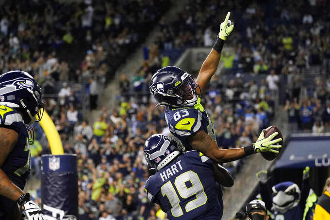 Seattle Seahawks wide receiver Darece Roberson Jr (83) celebrates with wide receiver Penny Hart (19) after Roberson caught a pass for a touchdown against the Los Angeles Chargers during the second half of an NFL football preseason game Saturday, Aug. 28, 2021, in Seattle. (AP Photo/Elaine Thompson)