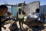 A woman receives donations in front of home destroyed by last week's tornado in El Roble, on the outskirts of Havana, Cuba, Wednesday, Feb. 6, 2019. For the first time in communist Cuba, prosperous individuals and successful private businesses have taken on an important role in disaster recovery. Hundreds of young people in jeans and designer t-shirts are hauling black plastic bags full of clothes, food and water donated by entrepreneurs, artists and other members of Cuba's independent upper-middle class to areas devastated by the tornado. (AP Photo/Ramon Espinosa)