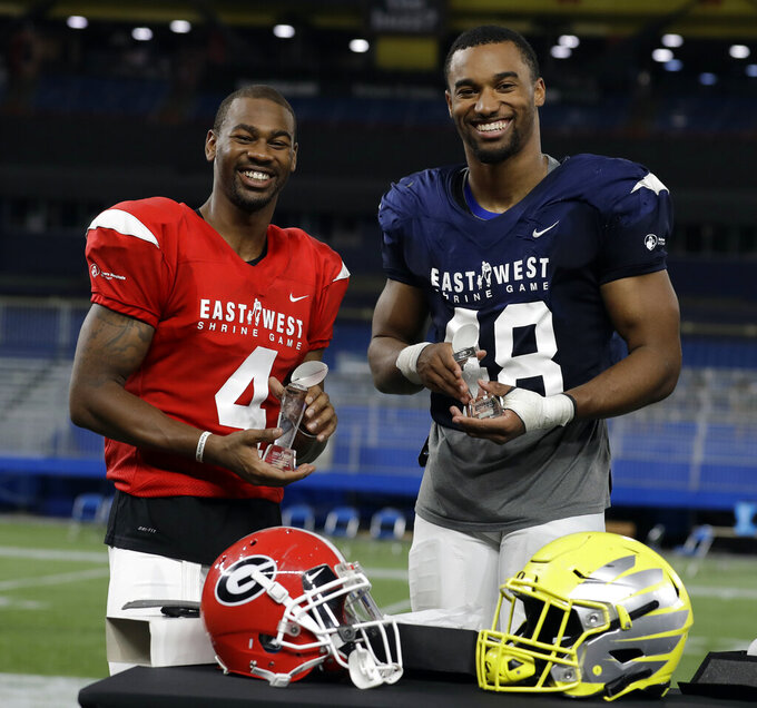East Wide receiver Terry Godwin II (4), of Georgia, and West linebacker Justin Hollins (48), of Oregon, pose with their trophies after being named MVP's of the East-West Shrine football game Saturday, Jan. 19, 2019, in St. Petersburg, Fla. (AP Photo/Chris O'Meara)