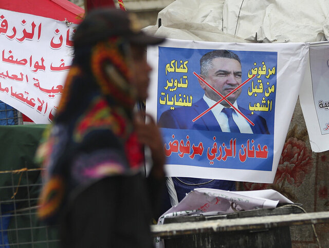FILE - In this Wednesday, March 18, 2020 file photo, an anti-government protester passes a defaced picture of Iraq's then Prime Minister-designate Adnan Al-Zurfi, in Tahrir Square, Baghdad, Iraq. On Thursday, April 9, 2020, Mustafa al-Kadhimi, Iraq's intelligence chief, has been appointed the country's third prime minister-designate in just over a month. The appointment comes after the resignation of Al-Zurfi, Thursday amid political infighting. The upheaval threatened a leadership vacuum at the helm of the government amid a severe economic crisis and viral pandemic. (AP Photo/Hadi Mizban, File)