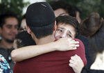 Youths comfort each other at the funeral of elementary school principal Elsa Mendoza, of one of the 22 people killed in a shooting at a Walmart in El Paso, in Ciudad Juarez, Mexico, Thursday, Aug. 8, 2019. Mexican officials have said eight of the people killed in Saturday's attack were Mexican nationals. (AP Photo/Christian Chavez)