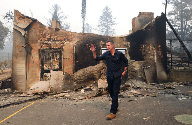 California Governor Gavin Newsom waves as he leaves the burned portion of Foothills Elementary School following a press conference near St. Helena, Calif., Thursday, Oct. 1, 2020.  (Christopher Chung/The Press Democrat via AP, Pool)