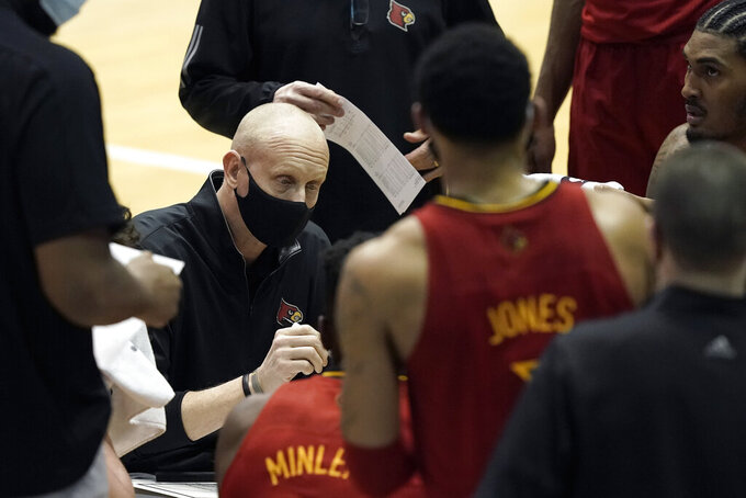 Louisville head coach Chris Mack speaks with his players during a timeout in the first half of an NCAA college basketball game against North Carolina in Chapel Hill, N.C., Saturday, Feb. 20, 2021. (AP Photo/Gerry Broome)