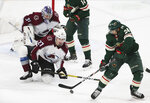 Colorado Avalanche's goalie Philipp Grubauer, top left, of Germany gets some defensive help from Colorado Avalanche's Ryan Graves as Minnesota Wild's Matt Dumba, right, reaches for a pass in the first period of an NHL hockey game Thursday, Nov. 21, 2019, in St. Paul, Minn. (AP Photo/Jim Mone)