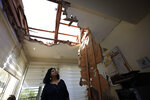 A woman looks at the damage to a house in Sderot, Israel, after it was hit by a rocket fired from Gaza Strip, Tuesday, Nov. 12m 2019. Israel has killed a senior Islamic Jihad commander in Gaza in a rare targeted killing that threatened to unleash a fierce round of cross-border violence with Palestinian militants. (AP Photo/Tsafrir Abayov)