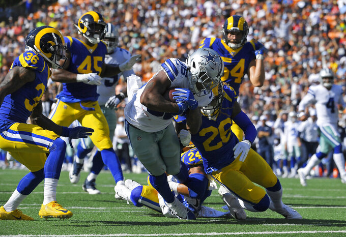 Dallas Cowboys running back Tony Pollard, center, runs in for a touchdown as Los Angeles Rams defensive back Marqui Christian, lower right, tries to tackle him during the first half of a preseason NFL football game Saturday, Aug. 17, 2019, in Honolulu. (AP Photo/Mark J. Terrill)