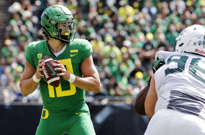 FILE - In this Sept. 8, 2018, file photo, Oregon quarterback Justin Herbert (10) looks for a receiver against Portland State during an NCAA college football game in Eugene, Ore. A couple of Pac-12 stars have a chance to put themselves into the Heisman mix on Saturday night when No. 7 Stanford visits No. 20 Oregon. Herbert has put up nice numbers in the first three weeks of the season, with 10 touchdown passes, no interceptions and 10.4 yards per attempt. He is not quite at the Tua level, but he's not that far off. (AP Photo/Thomas Boyd, File)