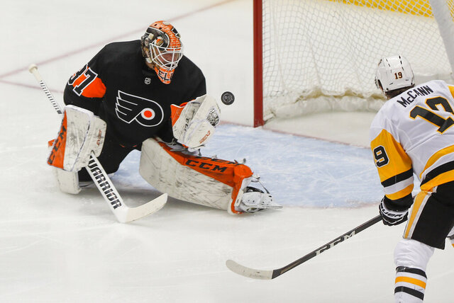 Pittsburgh Penguins' Jared McCann (19) waits for a rebound as Philadelphia Flyers goaltender Brian Elliott (37) stops a shot by Penguins' John Marino during the first period of an NHL hockey game Friday, Jan. 31, 2020, in Pittsburgh. (AP Photo/Keith Srakocic)