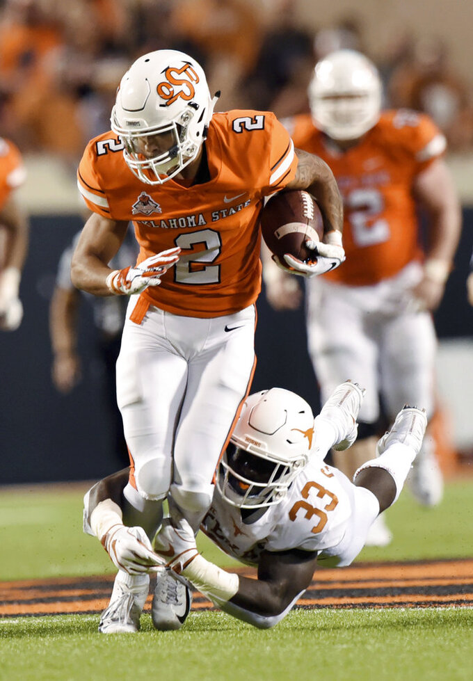 Texas linebacker Gary Johnson (33) tackles Oklahoma State wide receiver Tylan Wallace (2) in the second half of an NCAA college football game in Stillwater, Okla., Saturday, Oct. 27, 2018. Oklahoma State defeated Texas 38-35. (AP Photo/Brody Schmidt)