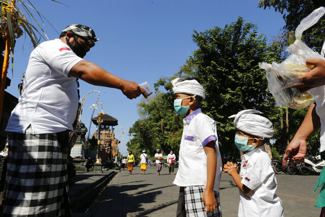 A security guard checks the body temperature of children at a temple amid new coronavirus outbreak in Bali, Indonesia Saturday, July 4, 2020. (AP Photo/Firdia Lisnawati)