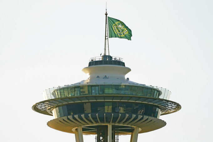 A flag with the new logo of the Seattle Storm WNBA basketball team flies on top of the Space Needle, Wednesday, March 3, 2021, in Seattle. Earlier in the day, the flag was raised by Storm guards Sue Bird, a four-time WNBA basketball champion who re-signed with the team earlier in the week, and Jordin Canada. (AP Photo/Ted S. Warren)