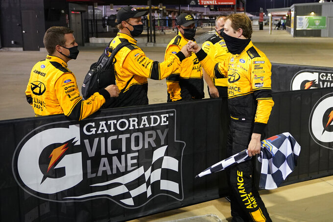 Brad Keselowski, right, shares a fist-bump with his team as he celebrates in Victory Lane after winning a NASCAR Cup Series auto race Saturday, Sept. 12, 2020, in Richmond, Va. (AP Photo/Steve Helber)