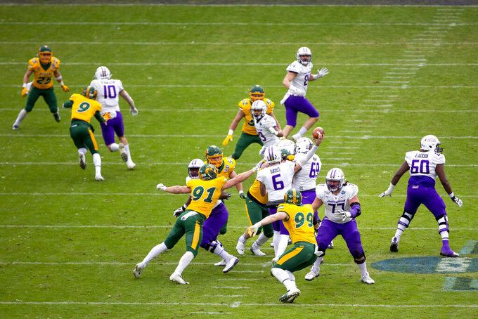 James Madison quarterback Ben DiNucci (6) throws a pass as North Dakota State defensive end Derrek Tuszka (91) attempts to tackle him during the first half of the FCS championship NCAA college football game, Saturday, Jan. 11, 2020, in Frisco, Texas. (AP Photo/Sam Hodde)