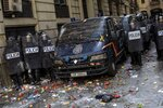 Spanish police stand outside a police station surrounded of objects thrown by pro-independence demonstrators in Barcelona, Spain, Friday, Oct. 18, 2019. Various flights into and out of the region are cancelled Friday due to a general strike called by pro-independence unions and five marches of tens of thousands from inland towns are expected converge in Barcelona's center on Friday afternoon for a mass protest with students to and workers who are on strike. (AP Photo/Bernat Armangue)