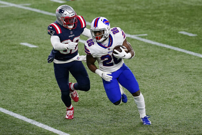 Buffalo Bills running back Devin Singletary carries the ball as New England Patriots defensive back Devin McCourty, left, gives chase in the first half of an NFL football game, Monday, Dec. 28, 2020, in Foxborough, Mass. (AP Photo/Elise Amendola)