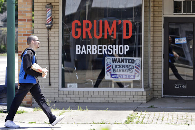 A man walks past Grum'D Barbershop, Friday, June 5, 2020, in Euclid, Ohio. Ohio Gov. Mike DeWine announced Friday that casinos, amusement parks and racetracks will be allowed to reopen June 19. (AP Photo/Tony Dejak)