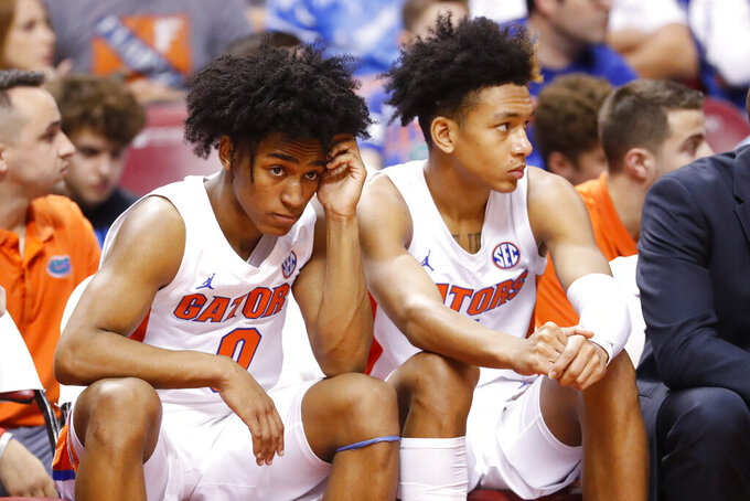 Florida guards Ques Glover (0) and Tre Mann sit on the bench in the second half of an NCAA college basketball game against Utah State, part of the Orange Bowl Classic tournament, Saturday, Dec. 21, 2019, in Sunrise, Fla. Utah State defeated Florida 65-62. (AP Photo/Wilfredo Lee)