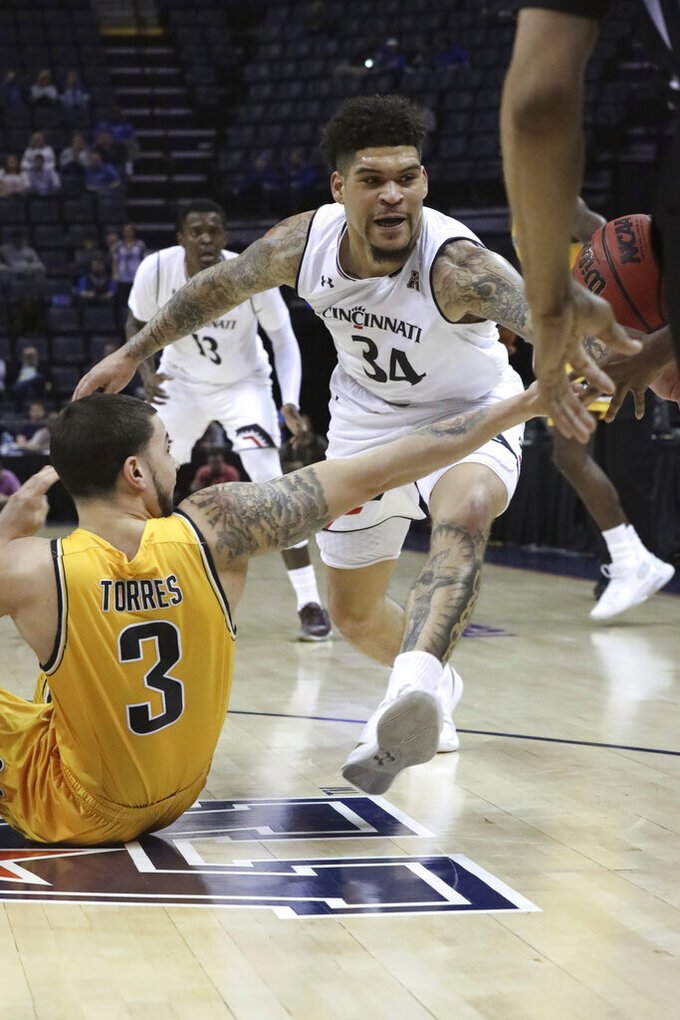 Wichita State player Rickey Torres tries to control a loose ball that is knocked away by Cincinnati's Jarron Cumberland in the first half of an NCAA college basketball game at the American Athletic Conference tournament Saturday, March 16, 2019, in Memphis, Tenn. (AP Photo/Troy Glasgow)