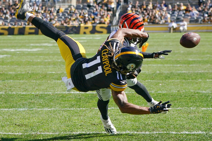 A penalty flag flies behind Pittsburgh Steelers wide receiver Chase Claypool (11) as he can't make a catch of a pass as Cincinnati Bengals cornerback Eli Apple (20) defends during the second half an NFL football game, Sunday, Sept. 26, 2021, in Pittsburgh. Apple was called for pass interference on the play. The Bengals won 24-10. (AP Photo/Gene J. Puskar)