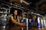 FILE - In this March 17, 2020, file photo bartender Courtney Schrag places beverage cans on the bar as she other employees prepare to close de Vere's Irish Pub in Sacramento, Calif. Local officials and businesses in the 13-county Greater Sacramento region were caught off guard last week when outdoor dining and worship services were OK again, hair and nail salons and other businesses could reopen, and retailers could allow more shoppers inside. It's still a mystery how the state made the decision or how and when it will lift the most serious restrictions on the bulk of the state's population because officials won't share their data. (AP Photo/Rich Pedroncelli, File)
