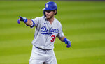 Los Angeles Dodgers' Cody Bellinger gestures to the dugout after pulling into second base with a double off Colorado Rockies relief pitcher Wade Davis to lead off seventh inning of a baseball game Friday, Sept. 18, 2020, in Denver. The Dodgers won 15-6. (AP Photo/David Zalubowski)