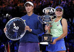 Sofia Kenin, right, of the U.S. holds the Daphne Akhurst Memorial Cup after defeating Spain's Garbine Muguruza in the women's singles final at the Australian Open tennis championship in Melbourne, Australia, Saturday, Feb. 1, 2020. (AP Photo/Lee Jin-man)