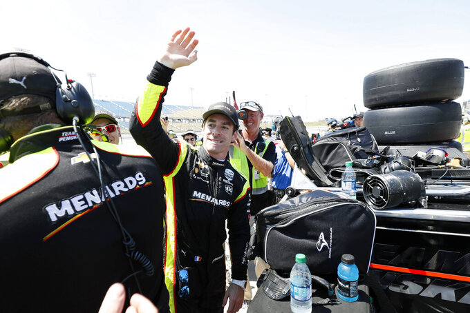 Simon Pagenaud celebrates with crew members after winning the pole position for an IndyCar Series auto race Friday, July 19, 2019, at Iowa Speedway in Newton, Iowa. (AP Photo/Charlie Neibergall)