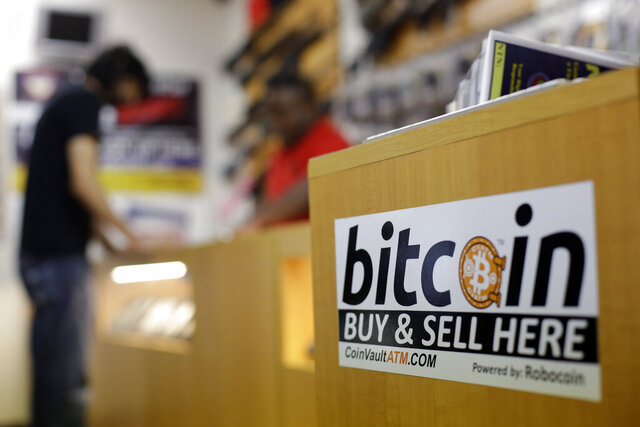 FILE - In this Wednesday, Aug. 20, 2014 file photo, Jon Rumion, background left, talks with Michael Cargill at Central Texas Gun Works in Austin, Texas. Bitcoin has crossed the $40,000 mark, extending on a huge rally that started three months ago, Thursday, Jan. 7, 2021.  (AP Photo/Eric Gay, File)