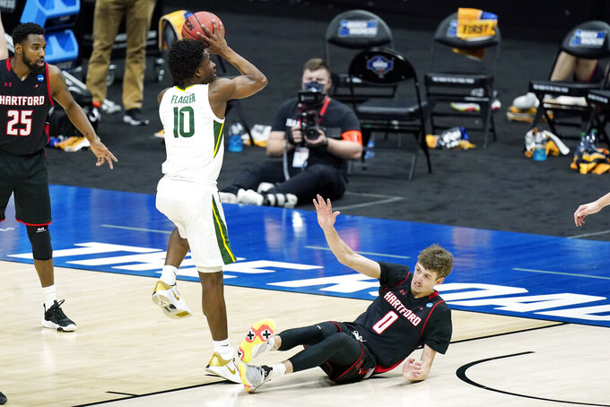 Hartford's Hunter Marks (0) falls as Baylor's Adam Flagler (10) drives to the basket during the first half of a college basketball game in the first round of the NCAA tournament at Lucas Oil Stadium in Indianapolis Friday, March 19, 2021, in Indianapolis, Tenn. (AP Photo/Mark Humphrey)