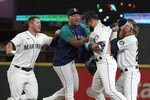 Seattle Mariners' Luis Torrens, second from right, is congratulated by teammates after his single scored Jarred Kelenic with the winning run during the ninth inning of the team's baseball game against the Texas Rangers, Wednesday, Aug. 11, 2021, in Seattle. The Mariners won 2-1. (AP Photo/Ted S. Warren)